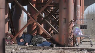 Homeless man sleeping on the ground under the bridge in cold autumn weather, covering himself with jacket. Cart with bin trash bags standing beside him. Homelessness, poverty and social issues concept