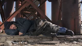 Homeless senior man in jacket sleeping outside in cold weather in city under the bridge. Senior beggar male covers his eyes with hat and tries to get warm, covering himself with jacket. Dolly shot