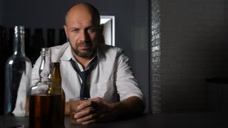Hopeless drunk middle-aged businessman with glass of alcohol beverage experiencing problems of alcohol abuse. Male sitting at the table over blurry wife with suitcase leaving her husband in background