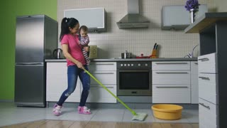 Housekeeping can be fun. Beautiful mother mopping the floor and dancing while holding her baby son in the kitchen at home. Happy housewife entertaining her infant child and doing housework. Dolly shot