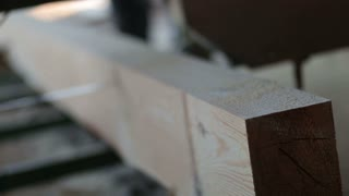 Industrial band-saw cutting timber into planks
