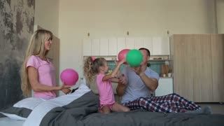 Joyful family playing with balloons on bed