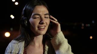 Joyful girl listening music with earphones at night