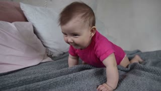 Joyful newborn child crawling on bed