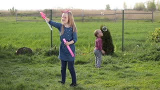 Joyful siblings playing with soap bubbles outdoors