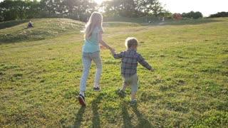 Joyful siblings running through green grassy field