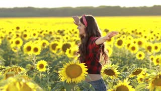 Joyful woman spinning around in sunflower field