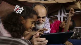 Kids teaching grandpa to use smart gadget