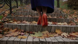 Lady in orange high heel shoes walking upstairs