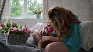 Laughing baby girl and mother relaxing in bedroom