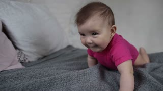 Laughing newborn child playing on bed