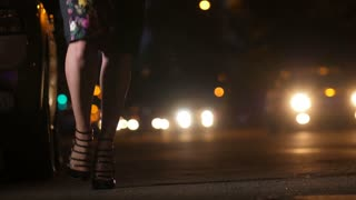 Legs of attractive businesswoman in high heeled stiletto shoes and pencil skirt walking at night on city street on bokeh traffic car lights background. Sexy lady in elegant footwear walking alone