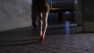 Legs of drunken woman in mini skirt and high stiletto shoes walking stumbling alone at night after party. Female feeling sick after alchohol abuse, she stops and throws up behind column in the tunnel