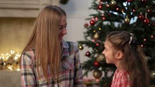 Little girl kissing her mother at Christmas