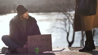 Lonely begging homeless man sitting on street at sunset at river bank while young woman passing by, sits near and shares a sandwich with bearded beggar male. Female talking to homeless mature man