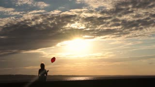 Lonely woman with heart balloon watching sunset