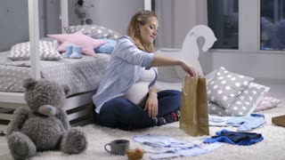 Lovely young adult pregnant female after shopping for newborn baby clothes. Expecting mother sitting in children's bedroom, unpacking shopping bag with cute baby boy clothing, putting it on the carpet