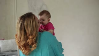 Loving mom kissing cute baby girl's nose