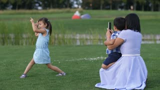 Loving mother taking pictures of funny, full of energy little asian daughter in summer park while holding son on lap. Playful preschool girl making funny faces while mom photographing her outdoors.