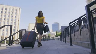 Low angle back view of business woman walking on high heels with luggage. Corporate female arrived on business trip and walking with suitcase in the city business area