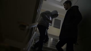 Low angle of drug addict buying drugs from a drug dealer in a dark building on stairway at night. Addict and dealer exchanging cash and heroin on staircase. Drug abuse, addiction, social issues