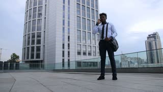 Low angle view of excited african american businessman celebrating his success, expressing positivity with winning gesture after phone call while standing outdoor with office building in background