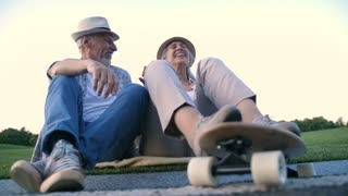 Low angle view of stylish senior married couple in hats sitting on sidewalk with skateboard, laughing and enjoying after skateboarding practive in summer park. Cheerful positive elderly couple
