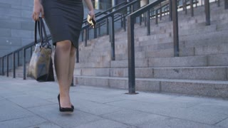 Low section of asian businesswoman in high heels and formal skirt with bag and smartphone in hands walking in business city area to job. Legs of office executive in a hurry going to workplace