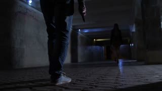 Male legs and hands with knife chasing lonely woman walking at night in dark pedestrian subway passage. Maniac chasing his prey in darkness. Female silhouette in mini skirt walking alone