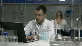 Male scientist working with tubes in laboratory