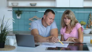 Man doing accounts together with his wife at home