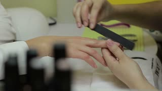 Manicurist filing client's nails with nail file