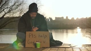 Mature homeless bearded man in hat and jacket sitting on street during sunset with cardboard sign and paper cup, and using his mobile phone at the river bank. Social issues concept, dolly shot.