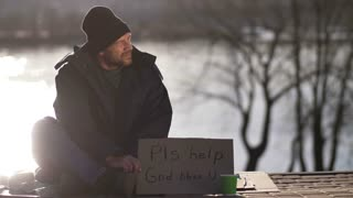 Mature male sitting on street on cold autumn day begging for money and holding cardboard sign Please help, god bless you. Senior man throws a few coins into homeless man's paper cup.