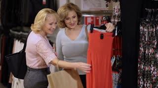 Mature women choosing dress in clothing store