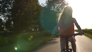Medium portrait shot of cute teenage blonde girl in eyeglasses riding bike and enjoying countryside views. Teen schoolgirl on adventure exploring nature. Sun flare during sunset. Steadicam shot