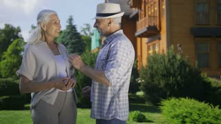 Medium shot of beautiful mature senior couple in front of new house. Handsome elderly man in hat giving door key to wife with grey hair. Happy wife and husband shaking keys to camera and smilingS