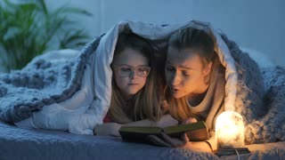 Middle-aged mother and her teen daughter in eyeglasses lying in bed under blanket and reading bedtime stories and fairytales together near a warm salt lamp at night. Family bonding, parenthood concept