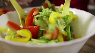 Middle aged woman cooking vegetable salad at home