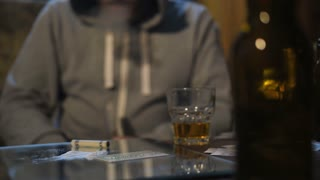Middle section of drug dealer and addict client sitting at the table in a dark domestic room exchanging money and cocaine. Marijuana fumes, cocaine lines on mirror, whiskey and beer bottles on table
