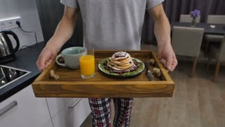 Midsection of male in pajamas holding wooden breakfast tray with delicious pancakes and orange juice and walking to serve it to his wife in bed. Slow motion steadicam stabilized shot