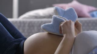 Midsection of pregnant female lying on her back and stepping with sweet small blue baby shoes on her big naked pregnant belly. Expecting mother playing with unborn child's shoes on her tummy. Dolly