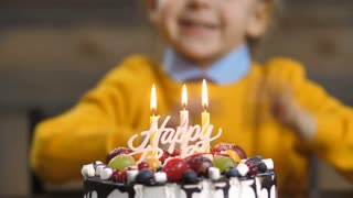 Midsection of sweet cheerful toddler boy, blowing candles on cake and clapping hands during his birthday party at home. Delicious cake on the foreground with blurry little excited child on background.