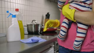 Midsection of young mother holding baby in her arms and cleaning kitchen surfaces with detergent. Housewife doing housework and keeping house clean together with her infant child. Dolly shot