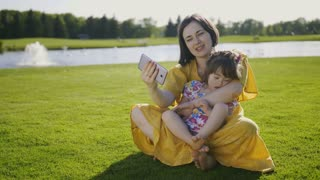 Mother and daughter with down syndrome sitting on green grass embracing making selfies on mobile phone. Mom and special needs girl grimacing and smiling at camera making self portraits on cellphone
