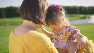 Mother and down syndrome daughter enjoying together outdoors on green grass meadow. Mom tickling little special needs girl making her laugh out of happiness. Funny family laughing together