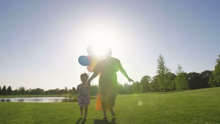 Mother and special needs toddler daughter holding hands and running together on green grass lawn on meadow at sunset with colorful baloons. Happy mom and girl with down syndrome laughing and enjoying