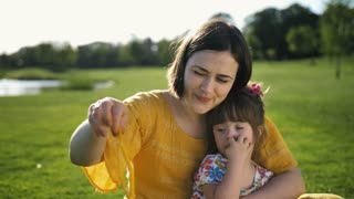 Mother sitting on green grass meadow with sweet little toddler daughter with down syndrome and blowing soap bubbles together. Happy family spending leisure together in summer nature