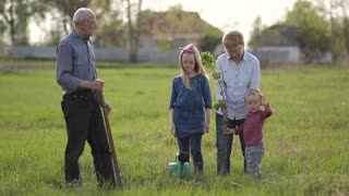Multi generation family planting tree outdoor