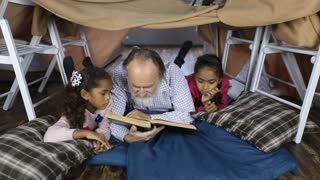 Old man reading the Bible with grandchildren